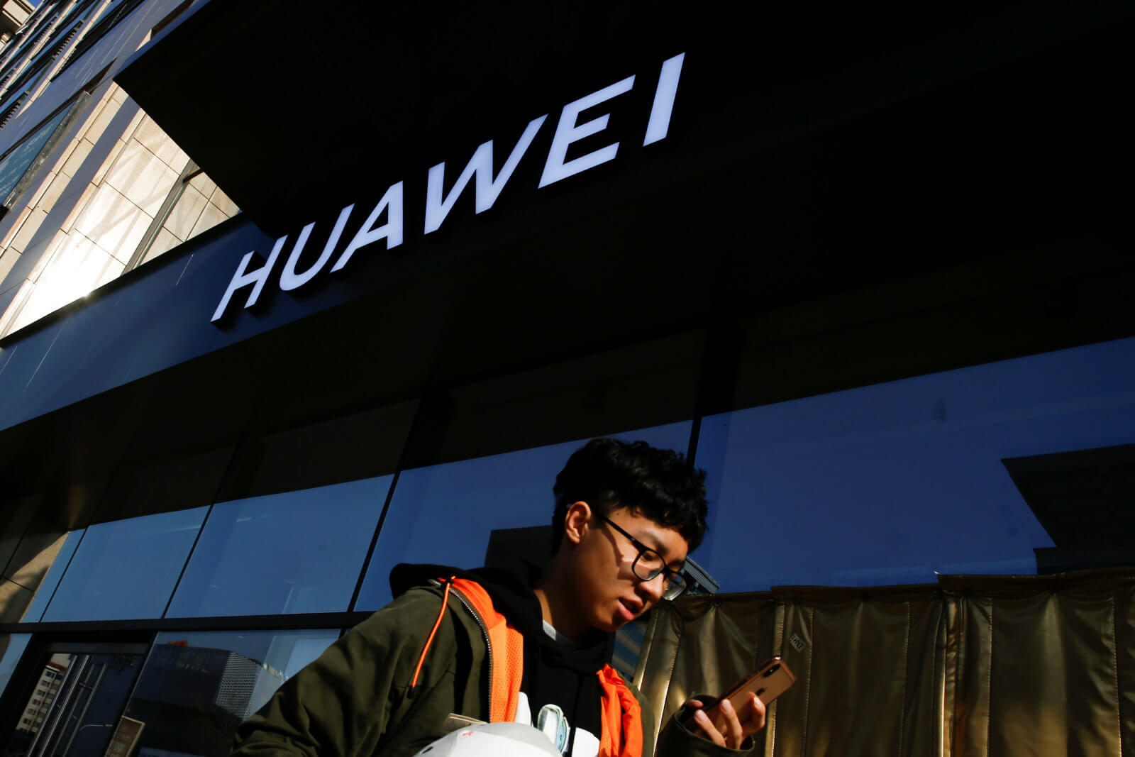 A man uses his phone as he walks past a Huawei shop in Beijing